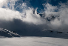 Swirling clouds surrounding the mountain tops in Switzerland Royalty Free Stock Image