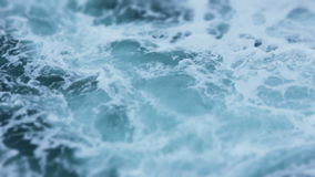 Swirling Foamy Ocean Sea Water. Static Medium long shallow depth of field shot of deep blue sea water waves swirling in the ocean, during a cloudy, rainy and