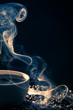 Swirling golden smoke taking away from coffee Stock Photo
