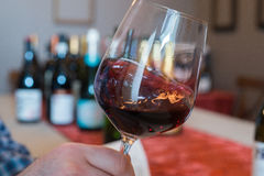 Swirling Red Wine in a Wineglass. Swirling white wine in a wineglass with bottles of wine in the background stock image