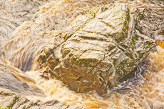 Swirling river water around rocks. Stock Images