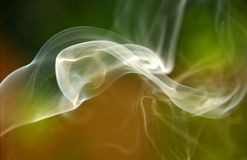 Swirling Smoke. Wafting smoke swirling against green and gold background Royalty Free Stock Images