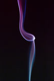 Swirling smoke from the incense on a homogeneous background Royalty Free Stock Images
