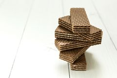 A swirling stack of chocolate wafers on a white table royalty free stock images