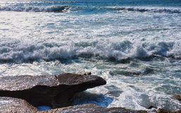 Swirling Pacific Ocean Waves Breaking over Rocks, Sydney, Australia. Swirling turbulent white foam Pacific Ocean waves crashing over coastal rocks, Cronulla royalty free stock image