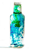 Swirling water. A bottle full of water with swirling colors merging into one royalty free stock photography