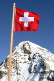 Swiss. The swiss flag on a background of beautiful mountain peaks Stock Photo