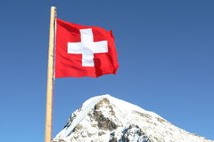 Swiss. The swiss flag on a background of beautiful mountain peaks Stock Image