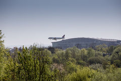 Swiss Air plane landing at Heathrow in front of Terminal 5. Swiss Air Airbus landing at Heathrow airport.  .  The trees in the foreground would need to make way Royalty Free Stock Photo