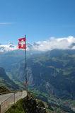 Swiss Alps. Swiss flag flying over the alps in the Bernese Oberland with the Lauterbrunnen valley below Stock Photos