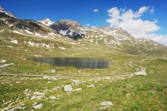 Swiss Alps. Bernina Pass, view of Alpine lake with railways in Switzerland Royalty Free Stock Image