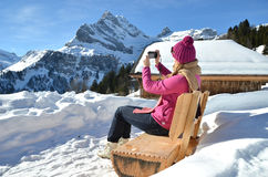 Swiss Alps. Girl taking a photo in the Swiss Alps Royalty Free Stock Images
