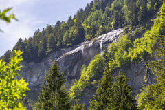 Swiss Alps seen through forest in Blausee or Blue Lake nature park, Switzerland Royalty Free Stock Image
