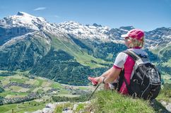 Swiss Alps. A traveler sitting on a cliff with a backpack admiri Stock Photography