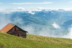 Swiss alps - view from mount Rigi. Swiss alps. View from mount Rigi in Central Switzerland. House in the foreground, lake Lauerz in the background Royalty Free Stock Images