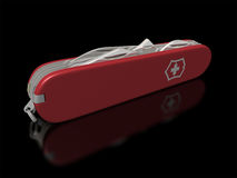 Swiss Army Knife. Isolated Swiss Army Knife on a reflective black background royalty free stock photography
