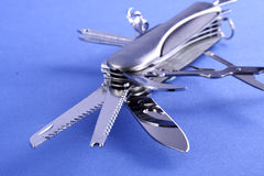 Swiss army knife. All-purpose Swiss army knife fully opened on blue background royalty free stock image