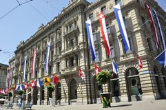 The swiss bank Credit Suisse Headquarter at Paradeplatz in Zürich. City decorated with the flags of the cantons stock photo