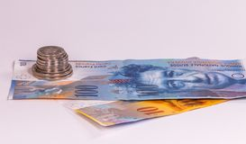 Swiss banknotes and coins on a white background stock images