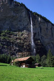 Swiss Cabin. Cabin home in the swiss alps with a beautiful waterfall behind it Stock Photo