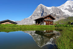 Swiss chalet. A swiss mountain chalet reflecting in a calm pond with the iconic north face of Eiger Mountain in the Bernese Alps, Switzerland royalty free stock photo