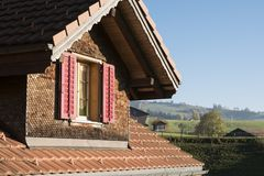 Swiss Chalet Attic Exterior: Roof and Window Stock Photo