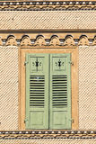 Swiss chalet with brown shingles and green window shutters Royalty Free Stock Images