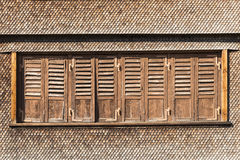 Swiss chalet with brown shingles and window shutters Royalty Free Stock Images