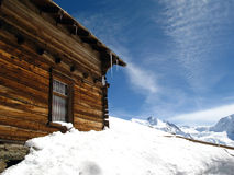 Swiss chalet Buried in Snow. Wooden chalet buried in snow in the Swiss Alps. Backdrop is blue sky and a bright sunny day stock image