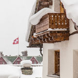 Swiss chalet. During heavy snow with Swiss flag in background Stock Photo