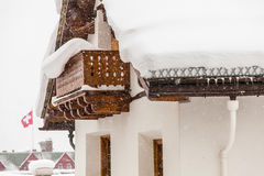 Swiss chalet. During heavy snow with Swiss flag in background Stock Photography