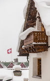 Swiss chalet. During heavy snow with Swiss flag in background Royalty Free Stock Photos