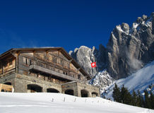 Swiss Chalet in winter. Chalet du Soldat, a remote refuge, hotel and restaurant in the pre-Alps from Fribourg area of Switzerland. In the background the rock stock photo