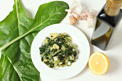 Swiss chard high angle. A side dish of swiss chard cooked in olive oil with garlic and chilli flakes and then tossed in lemon juice, with raw ingredients royalty free stock photos