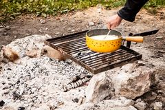 Swiss cheese fondue cooked in an outside firewood stock images