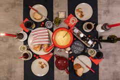 Swiss cheese fondue. Traditional swiss cheese fondue in a red pot on concrete dining table stock images