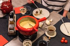 Swiss cheese fondue. Traditional swiss cheese fondue in a red pot on concrete dining table stock photos