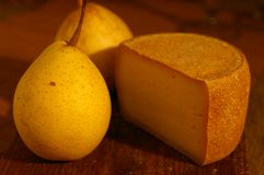 Swiss cheese and pear. Swiss cheese and yellow pear royalty free stock images