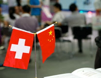 Swiss and Chinese flags at the business Stock Photos