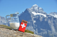 Swiss chocolate and jug of milk against mountain peak. Switzerla Stock Photography