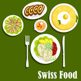 Swiss cuisine with rosti, fish and chocolate roll. Swiss national cuisine breakfast with potato rosti, topped with fried egg, fish steaks served with lemons Royalty Free Stock Image