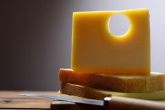 Swiss Emmental or Emmentaler medium-hard cheese with round holes made from cow milk in Canton Bern. Block of Swiss Emmental or Emmentaler medium-hard cheese with stock images