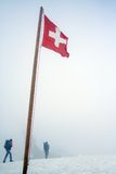 Swiss expeditors. Two expeditors walks in the snow, with the Swiss flag, Foggy scenery Royalty Free Stock Photography
