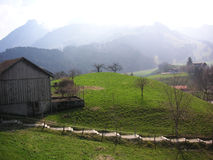 Swiss farm. A farm building in the Gruyere region of Switzerland, Alps in the background Royalty Free Stock Image