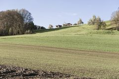 Agriculture in Switzerland. Swiss farmhouse surrounded by forests and plowed fields early in the morning. Agriculture in Switzerland, arable land and pastures Stock Image
