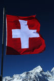 Swiss flag. The Swiss flag with mountains in the background Royalty Free Stock Photography
