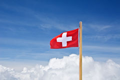 Swiss flag above clouds Royalty Free Stock Photo