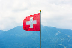 Swiss flag against Alps mountains Stock Photo