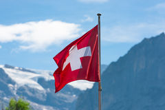 Swiss flag against Alps mountains Stock Images