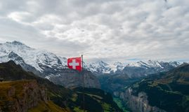 Swiss flag in the alps. Snow nature europe view beauty tourism high mountain peak cold jungfrau sharpen rock extremely background luxury coldly ice adventure stock images